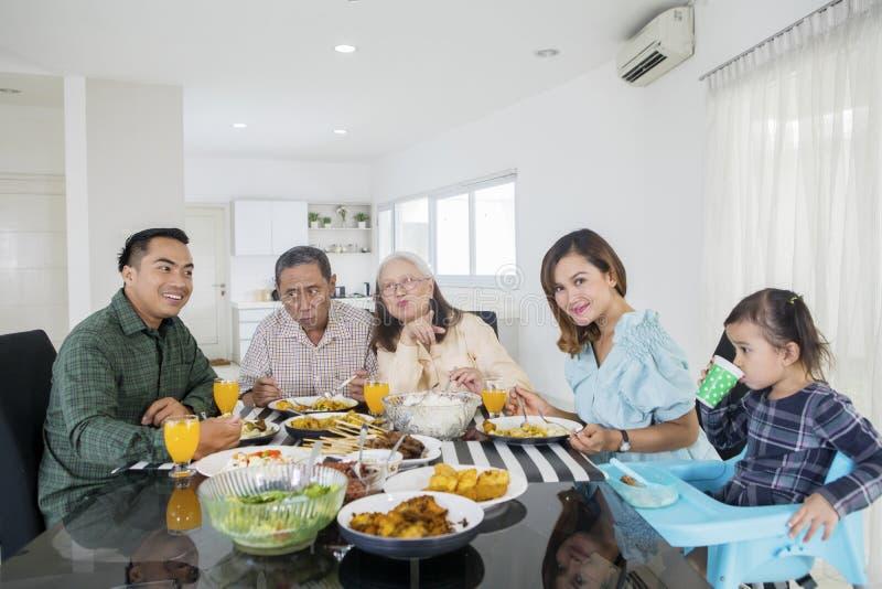 Famiglia allargata felice che mangia insieme i pasti fotografia stock libera da diritti
