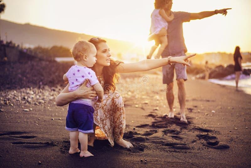 Famiglia allegra che cammina sulla spiaggia tropicale immagine stock