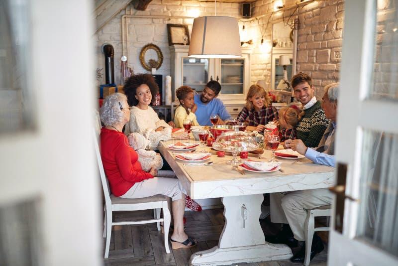 Famiglia allegra che celebra tempo di Natale e godere della cena di Natale immagini stock