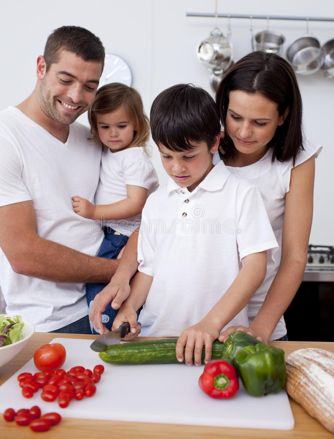 Famiglia allegra che cucina insieme le verdure fotografie stock
