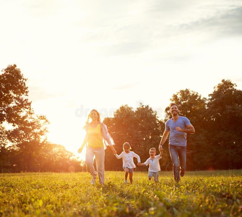 Famiglia allegra che gode insieme fuori fotografia stock