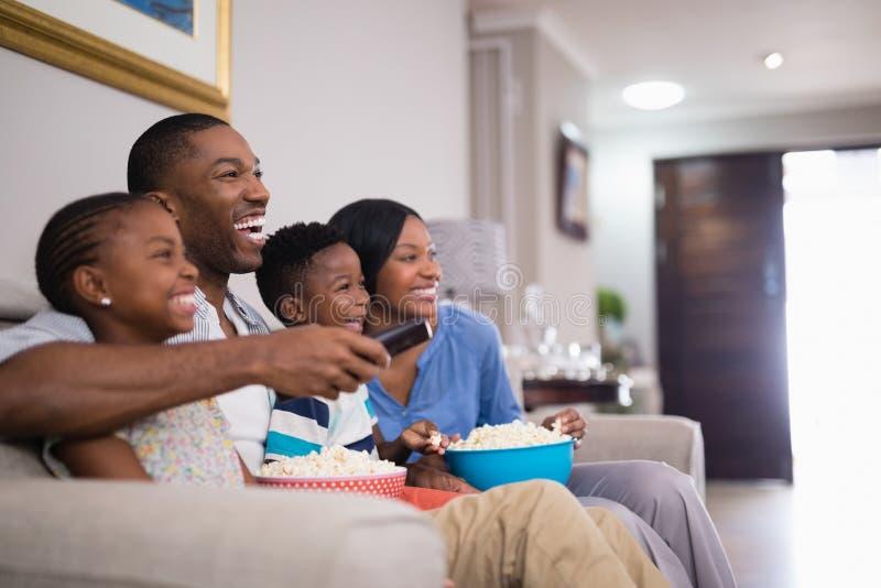 Famiglia allegra che mangia popcorn mentre guardando televisione fotografia stock