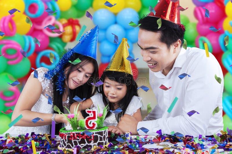 Famiglia allegra che taglia una torta di compleanno fotografia stock