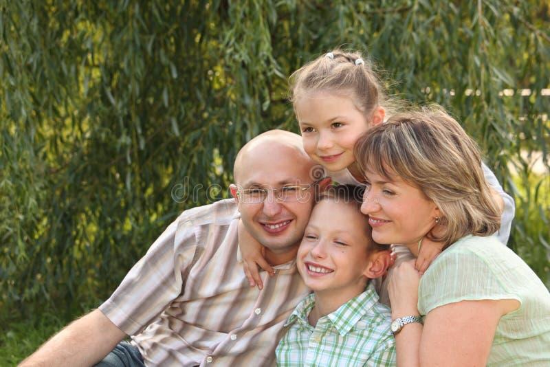 Famiglia allegra con due bambini nella sosta di caduta immagini stock