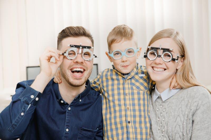 Famiglia allegra con il piccolo oftalmologo di medico di ricezione del bambino facendo uso dei vetri fotografie stock libere da diritti
