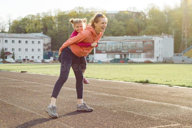 Famiglia allegra di sport, stile di vita sano, ritratto della molla della madre e piccola figlia divertendosi e mantenendo allo s immagine stock