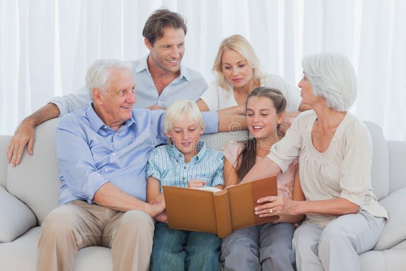 Famiglia allegra estesa che esamina un album di foto immagine stock libera da diritti
