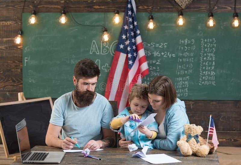 Famiglia americana allo scrittorio con il figlio che fa gli aerei di carta Concetto di Homeschooling Genitori che insegnano al fi fotografia stock