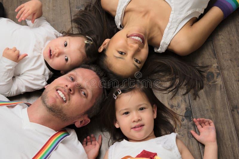 Famiglia americana asiatica della corsa mista che mette su pavimento che esamina macchina fotografica fotografia stock libera da diritti