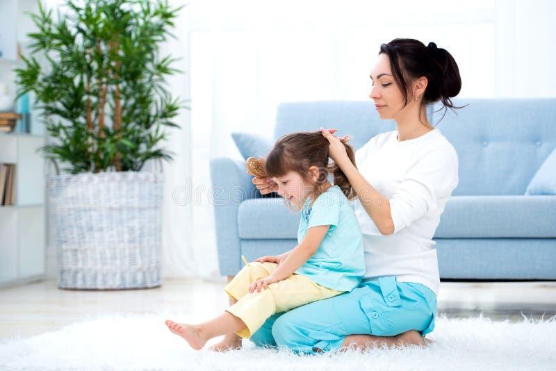 Famiglia amorosa felice La madre sta pettinando la seduta dei capelli di sua figlia sul tappeto sul pavimento nella stanza fotografie stock libere da diritti