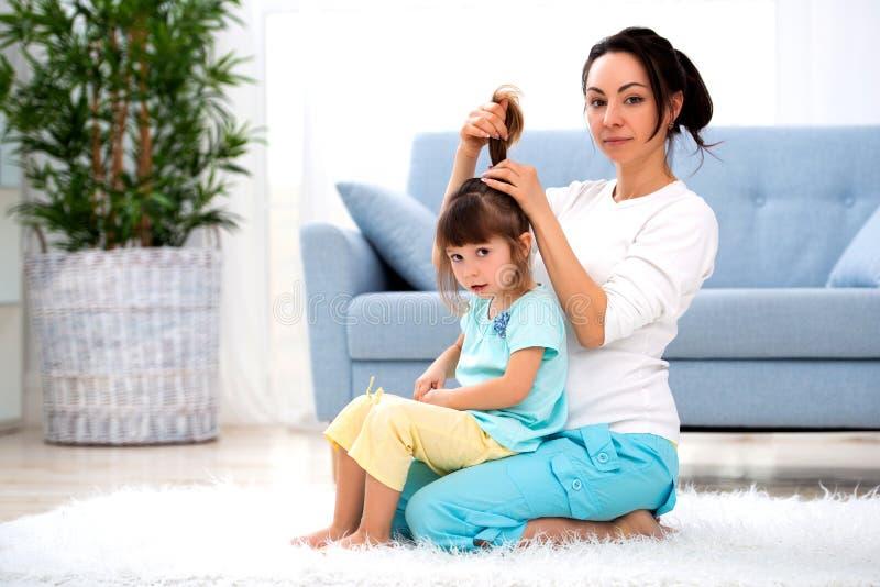 Famiglia amorosa felice La madre sta pettinando la seduta dei capelli di sua figlia sul tappeto sul pavimento nella stanza fotografia stock libera da diritti