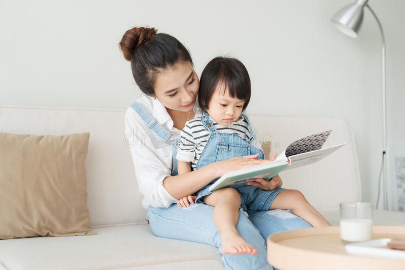 Famiglia amorosa felice Madre asiatica abbastanza giovane che legge un libro a fotografia stock libera da diritti