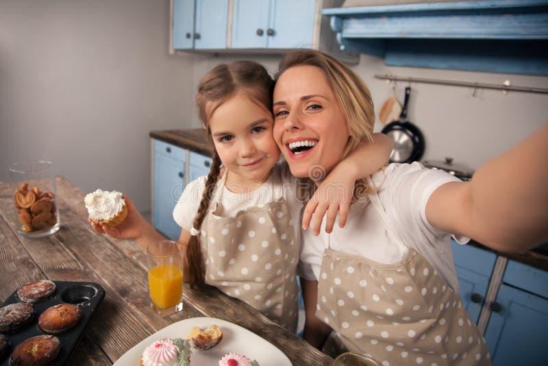 Famiglia amorosa felice nella cucina La ragazza della figlia del bambino e della madre sta mangiando i biscotti che hanno fatto e fotografia stock