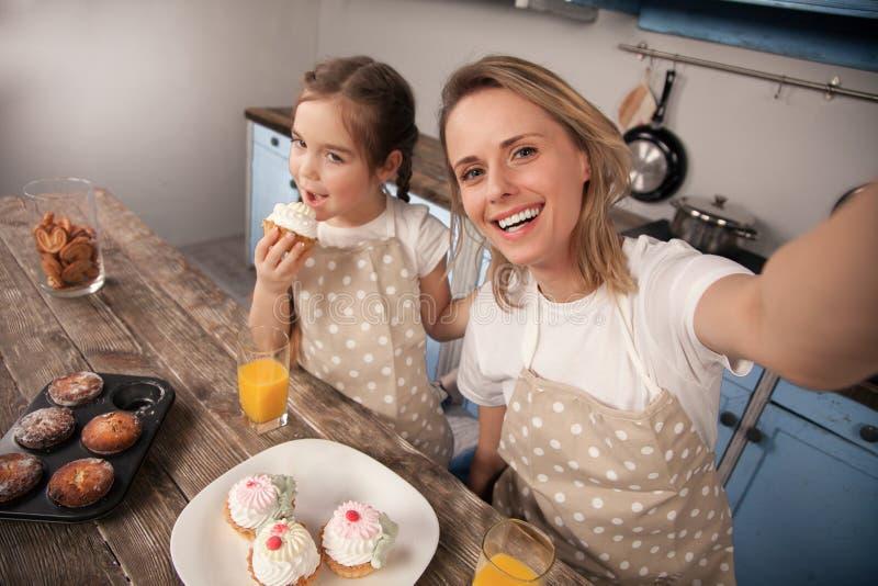 Famiglia amorosa felice nella cucina La ragazza della figlia del bambino e della madre sta mangiando i biscotti che hanno fatto e fotografia stock libera da diritti
