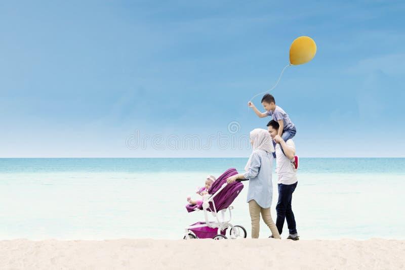 Famiglia asiatica che cammina insieme sulla riva fotografie stock libere da diritti