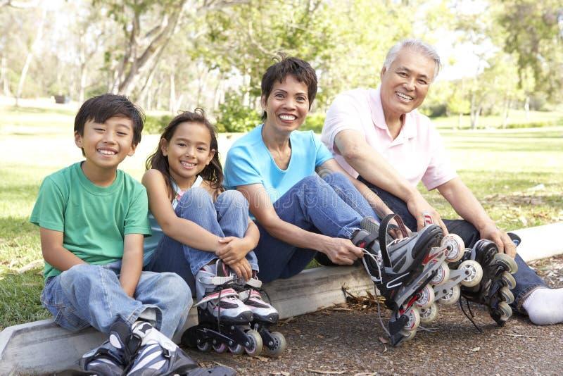 Famiglia asiatica che mette sopra nella riga pattini nella parità immagine stock