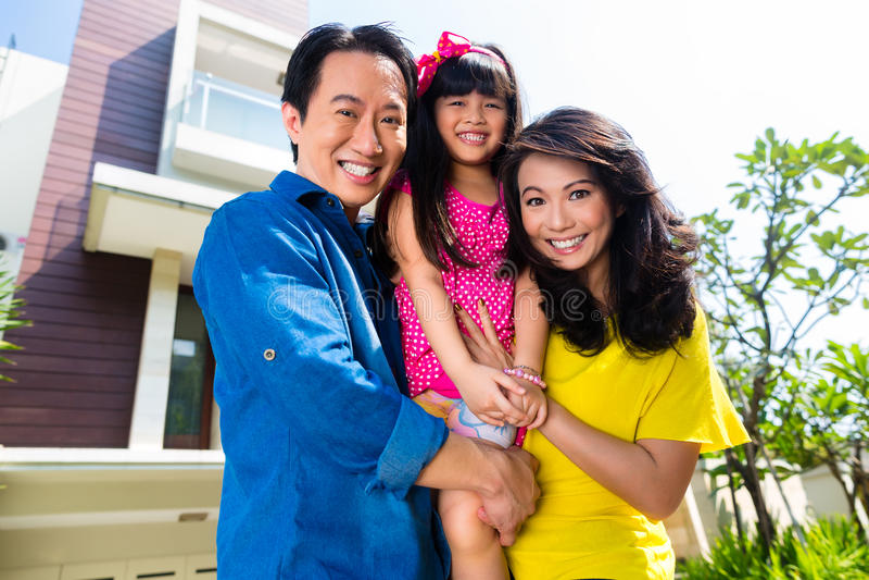 Famiglia asiatica con il bambino che sta davanti alla casa immagini stock libere da diritti