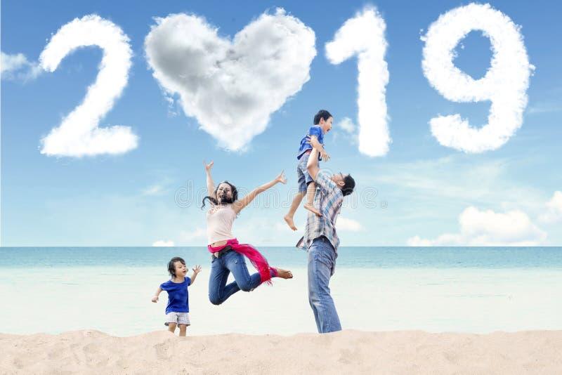 Famiglia asiatica con il numero 2019 sulla spiaggia immagine stock