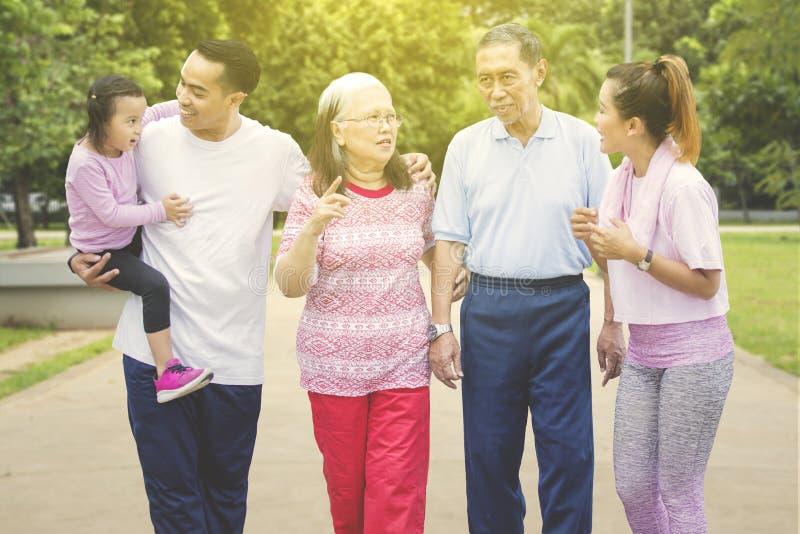 Famiglia asiatica della famiglia allargata che chiacchiera nel parco fotografia stock
