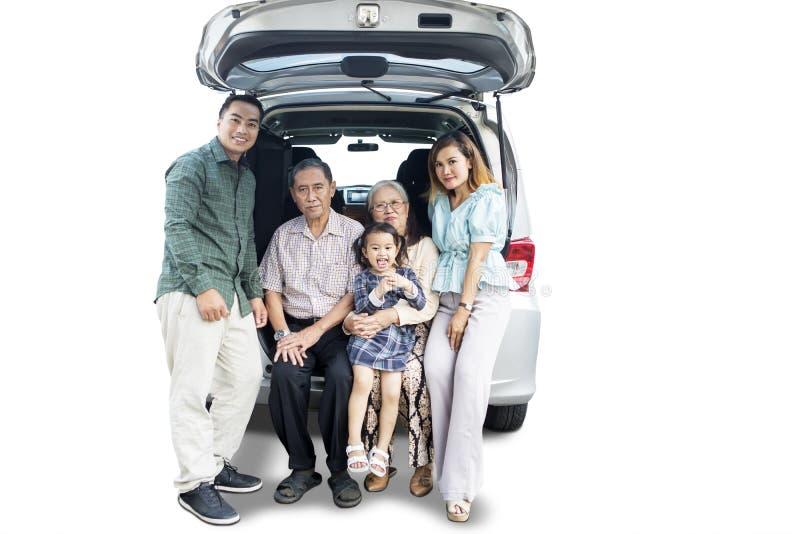 Famiglia asiatica estesa che si siede nel tronco di automobile immagine stock