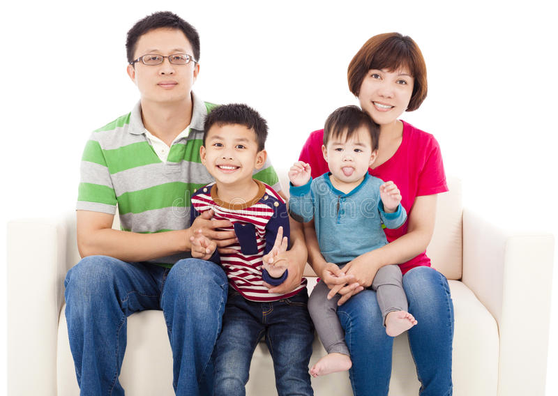 Famiglia asiatica felice che si siede su un sofà del cuoio bianco fotografie stock