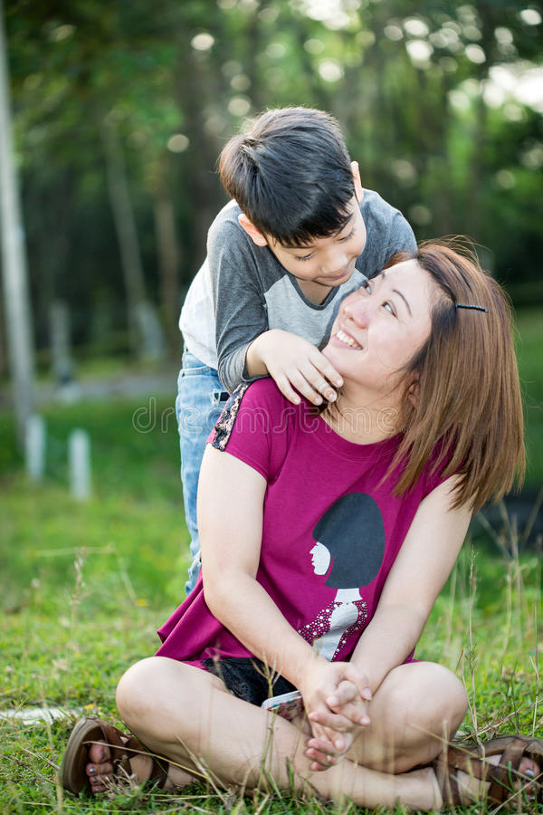 Famiglia asiatica felice, madre con suo figlio al parco fotografie stock