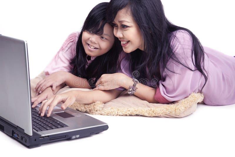 Famiglia asiatica felice su un computer portatile fotografia stock libera da diritti