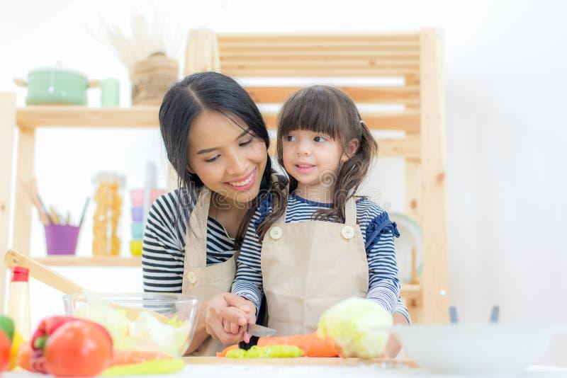 Famiglia in buona salute Ragazza del bambino e della madre che cucina e che taglia le verdure per la dieta sulla cucina immagine stock libera da diritti