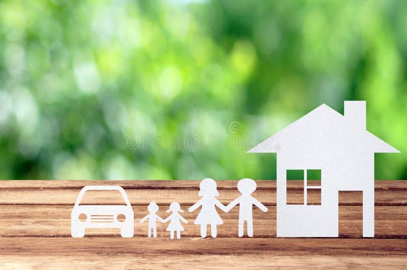 Famiglia, casa ed automobile di carta sulla tavola di legno con il ou del bokeh del giardino fotografia stock libera da diritti