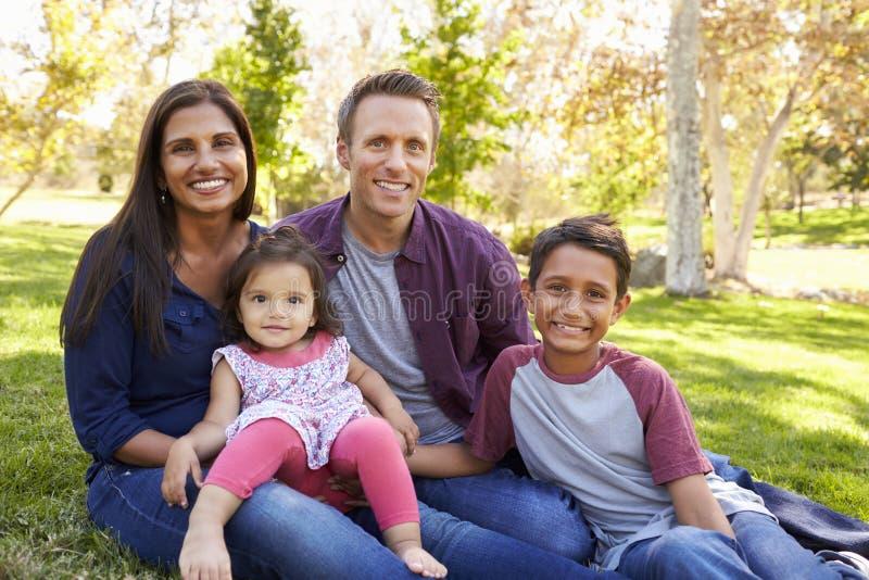 Famiglia caucasica asiatica felice della corsa mista, ritratto in un parco fotografie stock