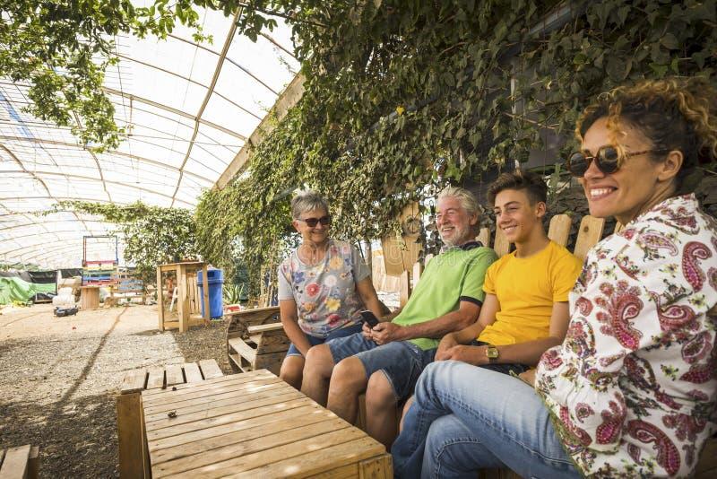 Famiglia caucasica nella seduta di amicizia e di relazione all'aperto in un posto naturale fatto con legno riciclato dai grandfth fotografia stock libera da diritti