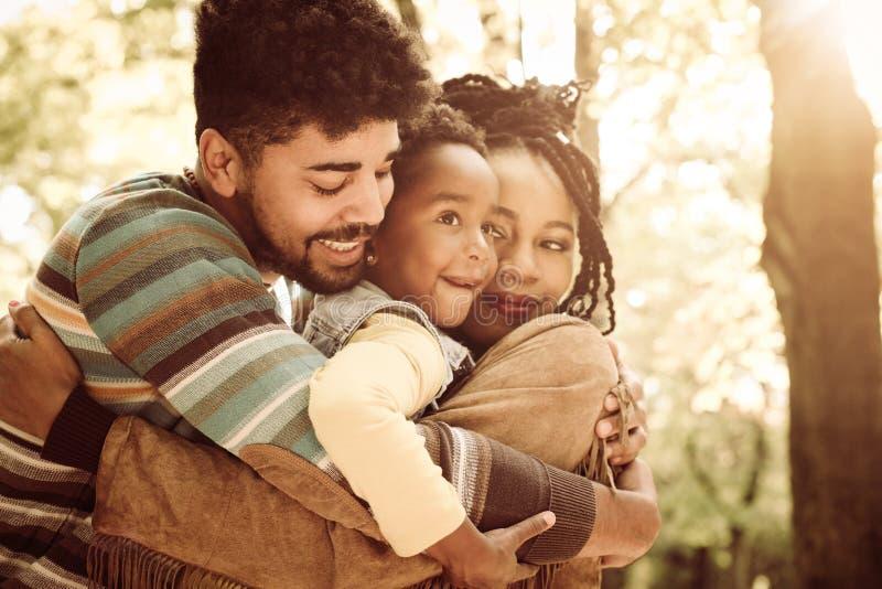 Famiglia che abbraccia insieme e che gode nel parco fotografia stock