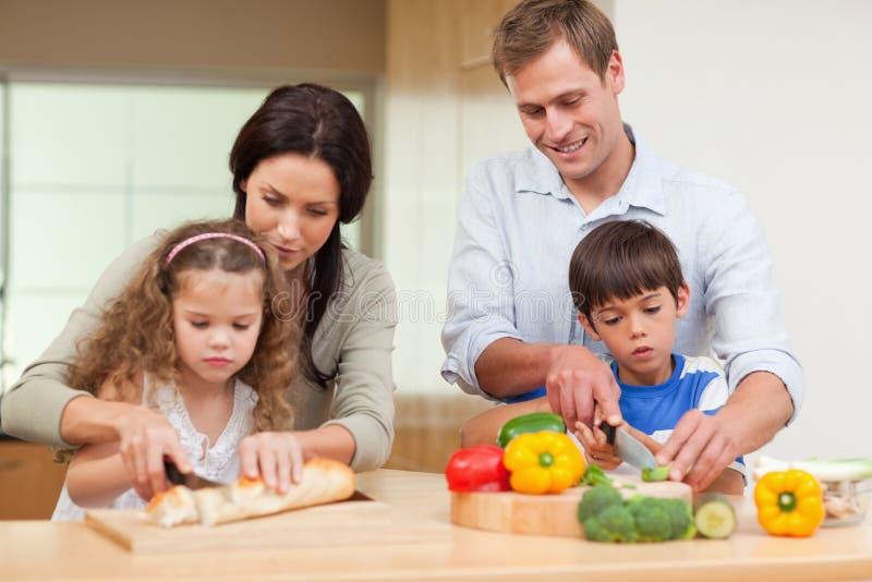 Famiglia che affetta gli ingredienti fotografia stock