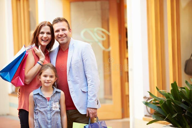 Famiglia che cammina attraverso il centro commerciale con i sacchetti della spesa fotografie stock