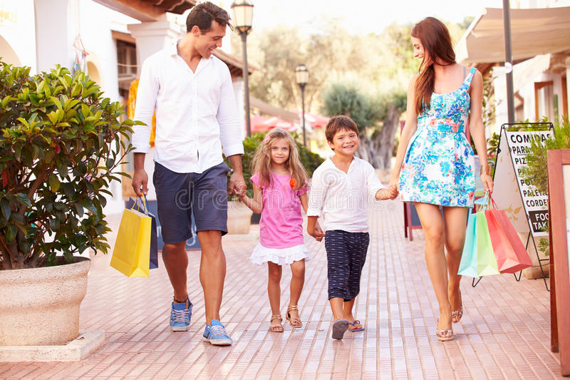 Famiglia che cammina lungo la via con i sacchetti della spesa fotografie stock