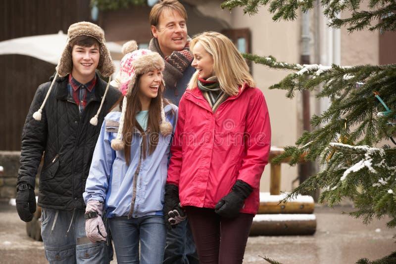 Famiglia che cammina lungo la via della città nella stazione sciistica immagini stock