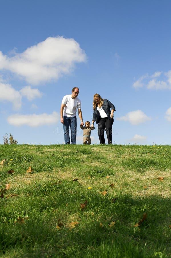 Famiglia che cammina sul campo fotografia stock libera da diritti