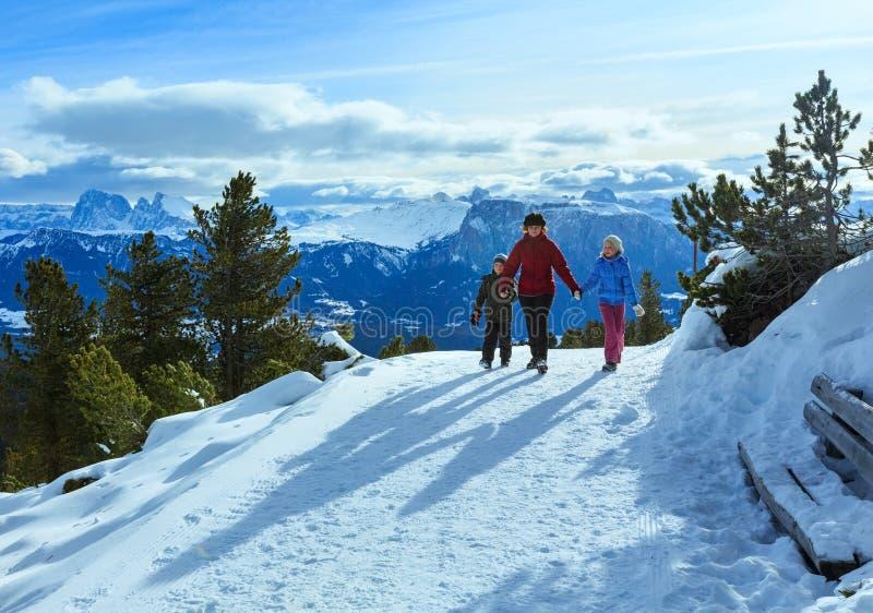 Famiglia che cammina sul pendio di montagna di inverno fotografie stock