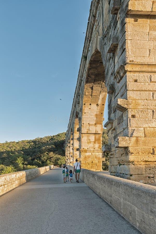 Famiglia che cammina sull'aquedotto romano Pont du il Gard La Francia, Europa fotografie stock libere da diritti
