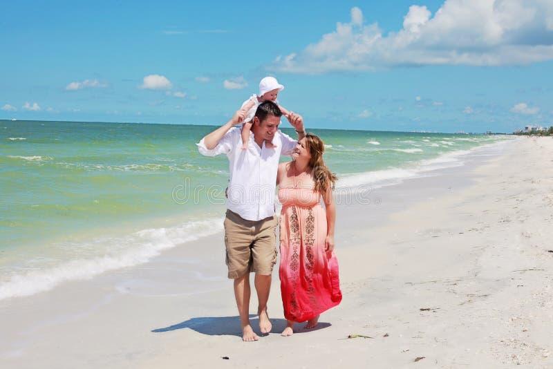 Famiglia che cammina sulla spiaggia immagini stock libere da diritti