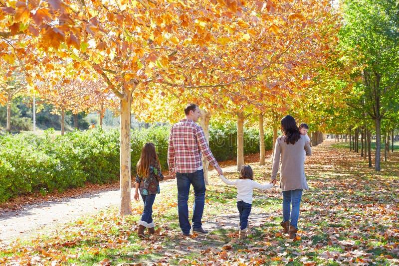 Famiglia che cammina in un parco di autunno fotografie stock