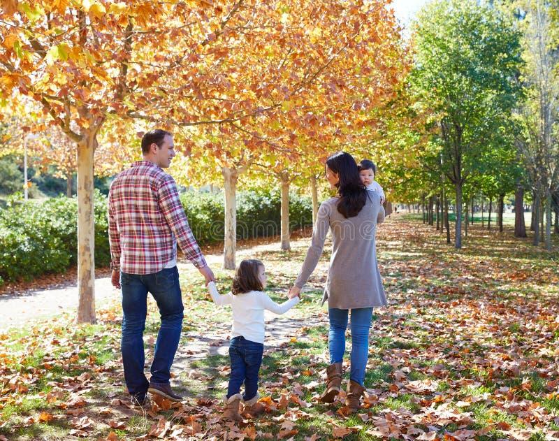 Famiglia che cammina in un parco di autunno fotografia stock