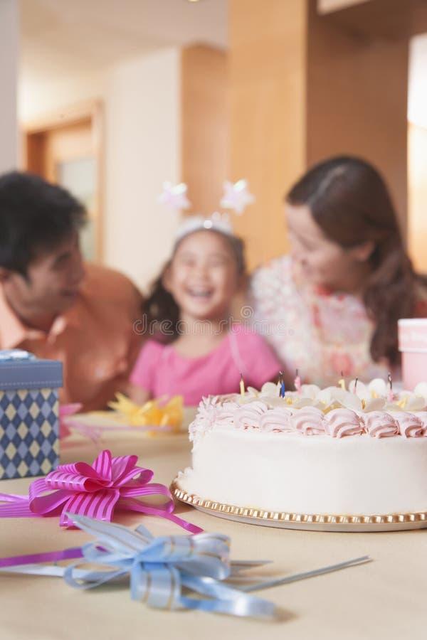 Famiglia che celebra il compleanno della ragazza - fuoco sulla torta di compleanno fotografia stock libera da diritti