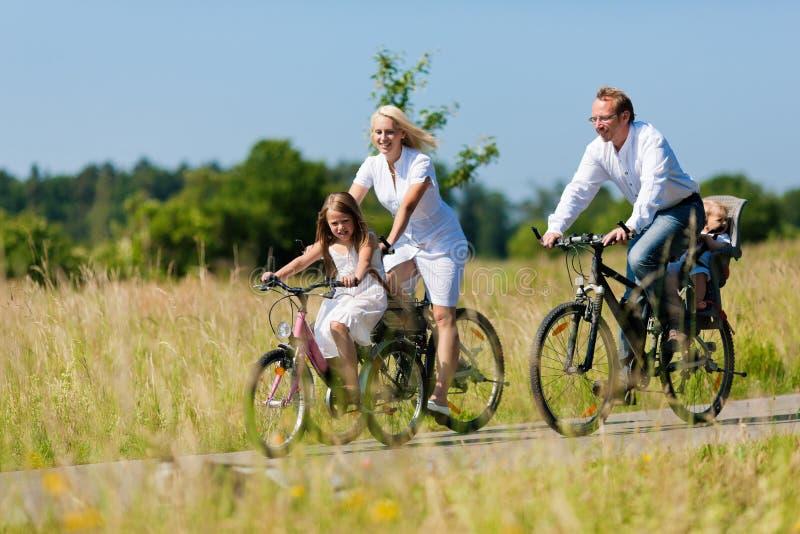 Famiglia che cicla all'aperto in estate immagine stock libera da diritti
