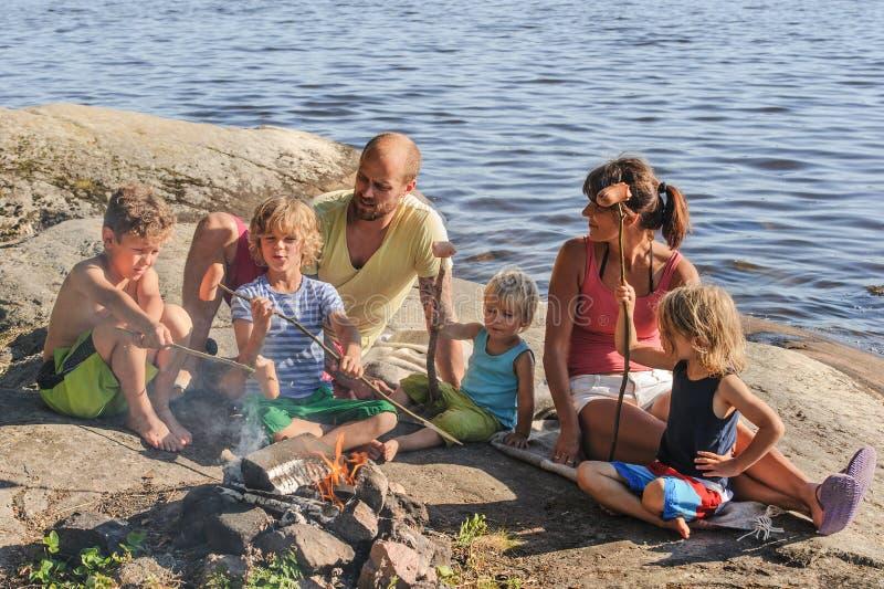 Famiglia che cucina al fuoco di accampamento fotografia stock libera da diritti