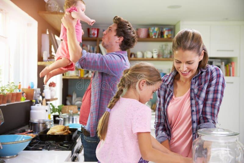 Famiglia che cucina insieme pasto in cucina immagine stock