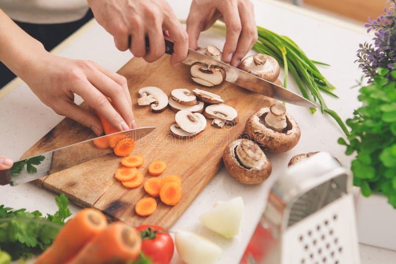 Famiglia che cucina la preparazione del pasto che taglia insieme gli ingredienti immagini stock libere da diritti
