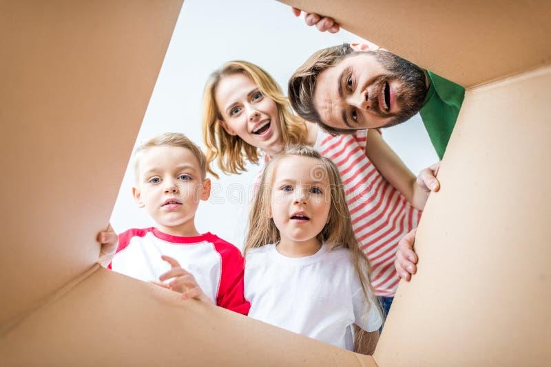 Famiglia che dà una occhiata dalla scatola di cartone immagini stock libere da diritti