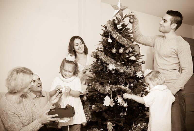 Famiglia che decora l'albero del nuovo anno immagini stock