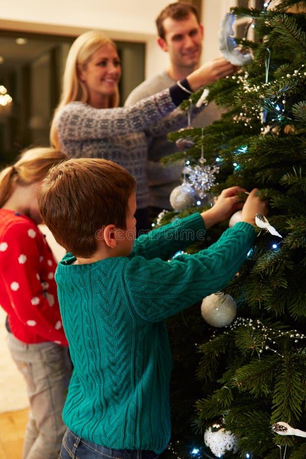 Famiglia che decora l'albero di Natale a casa insieme fotografia stock